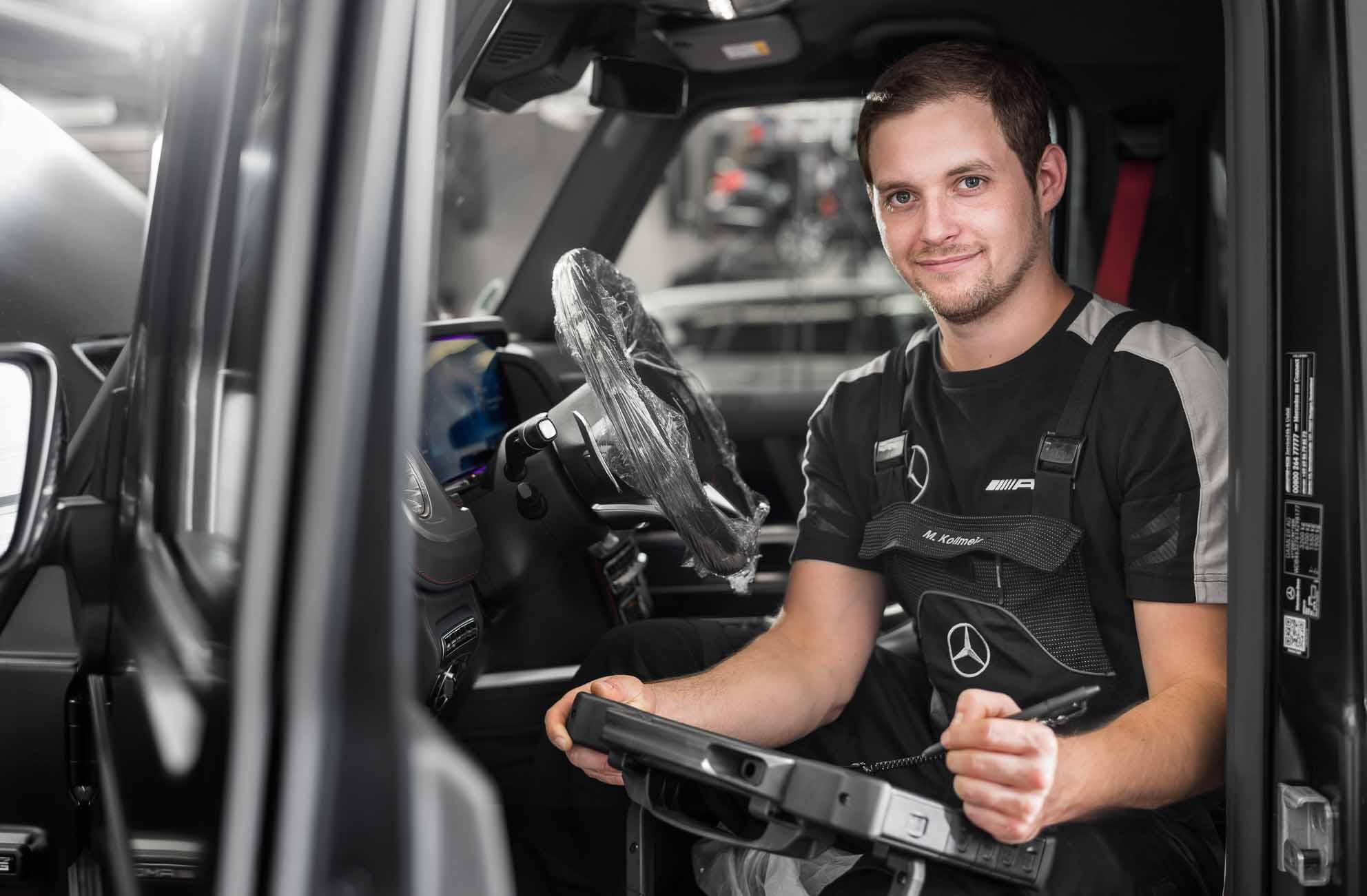 Das Bild zeigt einen Mechatroniker der in einer G-Klasse mit einem Messgerät sitzt. Die Fotografie ist in der Mercedes AMG Werkstatt in Dortmund während eines Businessshooting entstanden.
